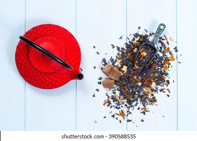 Traditional Japanese red teapot and tea leaves on wooden table
