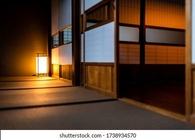 Traditional japanese room low angle view in house or ryokan with open shoji sliding paper doors tatami mat floor and lamp illuminated at night with nobody