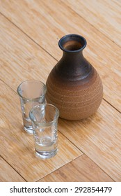 Traditional Japanese Sake with two cups on the wood.
