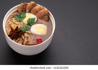 Traditional Japanese soup ramen with meat broth, asian noodles, seaweed, sliced chiken, eggs. Close up. Asian style food. Top view. Hot tasty ramen soup for dinner. Dark background.