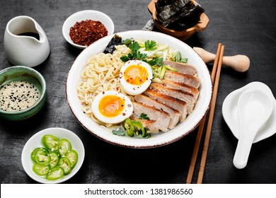 Traditional Japanese soup ramen with meat broth, asian noodles, sliced pork and eggs .  Asian style food.