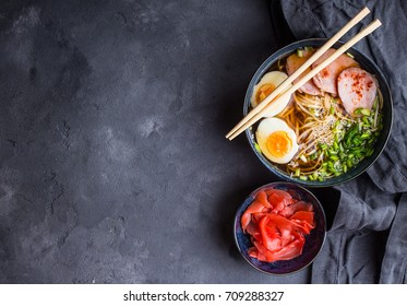 Traditional Japanese soup ramen with meat broth, asian noodles, seaweed, sliced pork, eggs and pickled ginger. Background. Asian style food. Space for text. Top view. Hot tasty ramen soup for dinner