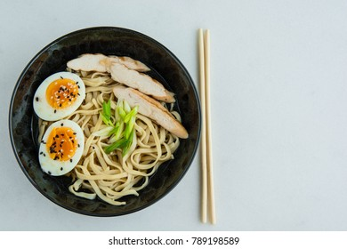 Traditional Japanese soup ramen with meat broth, asian noodles, seaweed, sliced chiken, eggs. Close up. Asian style food. Top view. Hot tasty ramen soup for dinner.