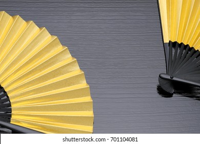 traditional Japanese style golden hand fan on gray background?