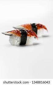 Traditional japanese sushi nigiri with smoked eel on a white background, vertical shot. Unagi smoked eel top view