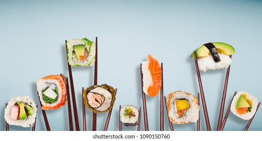 Traditional japanese sushi pieces placed between chopsticks, separated on light blue pastel background. Very high resolution image.
