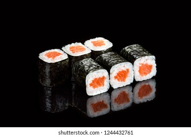 Traditional japanese sushi roll with salmon close up isolated on a black backround