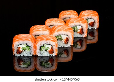 Traditional japanese sushi roll with  smoked salmon  close up isolated on a black backround