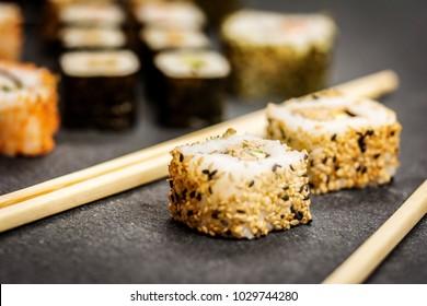 Traditional japanese sushi rolls hosomaki,uramaki  and chopsticks  on stone desk
