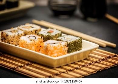 Traditional japanese sushi rolls hosomaki,uramaki  and chopsticks and soy sauce on stone desk