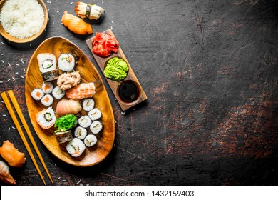Traditional Japanese sushi and rolls with soy sauce and ginger. On dark rustic background