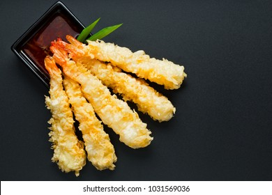 Traditional japanese tempura shrimps  with sauce, deep fried shrimps top view on the background