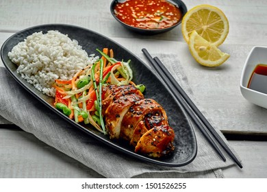 Traditional Japanese teriyaki chicken with salad made of cucumber, ginger, carrot, pepper and cabbage, rice, sesame, chili and soy sauces, lemon and edamame.