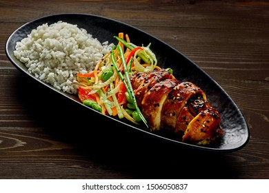 Traditional Japanese teriyaki chicken with salad made of cucumber, ginger, carrot, pepper and cabbage, rice, sesame and edamame on a rustic wooden table.