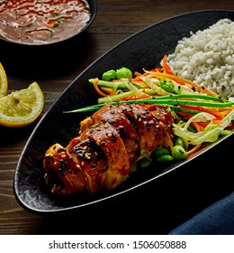 Traditional Japanese teriyaki chicken with salad made of cucumber, ginger, carrot, pepper and cabbage, rice, sesame and edamame.