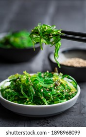 Traditional Japanese wakame salad with sesam seeds on black background. Healthy and fresh seaweed salad.