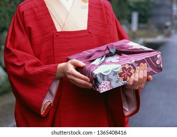 Traditional Japanese Woman in Kimono Dress Holding a Gift