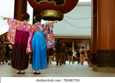 Traditional Japanese women dressed in Kimono posing at the entrance of Senso-ji temple, Asaukusa, Tokyo, Japan