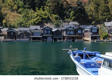 The traditional Japanese wooden fishing houses, Funaya, in Ine, Kyoto, Japan. Each house has a dock for the boat. A cherry tree in full blossoming.