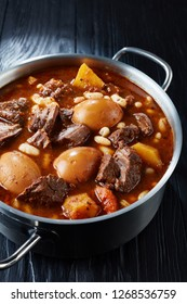 Traditional Jewish Cholent Hamin - main dish for the Shabbat meal slow cooked beef with potato, beans and brown eggs in a pot on a black wooden table, vertical view from above, close-up