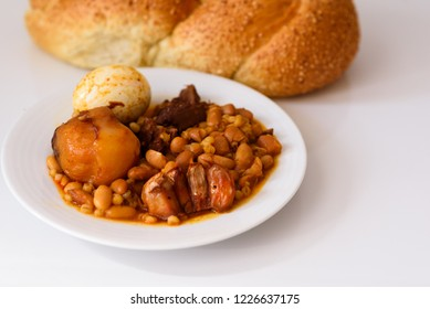 Traditional Jewish Cholent (Hamin) prepared in Israel, the main dish for the Shabbat meal made with beef, potato, beans, barley, eggs, wheat, garlic and served with challah-special bread for Sabbath.