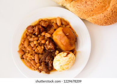 Traditional Jewish Cholent (Hamin) special Slow Cooked Stew in Jewish cuisine, main dish for the Shabbat  made with beef, potato, beans and more and served with challah - bread for Sabbath. Top view.