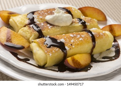 Traditional Jewish food cheese blitzes with whipped cream, peaches and chocolate sauce in closeup