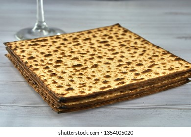 Traditional Jewish kosher matzo for Passover macro on a wooden table. Matzah or matzo, unleavened bread for Pesach, Jewish holiday of Passover, design element.