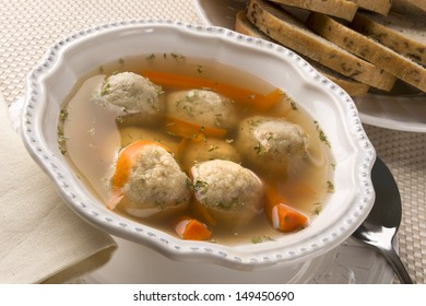 Traditional Jewish passover dish matzah ball soup served with rye bread