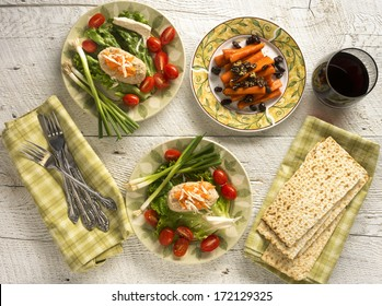 Traditional Jewish Passover dishes of Gefilte Fish and Tsimmes with red wine and matzah on white wood