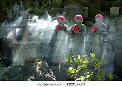 Traditional Jizo statue and incense smoke