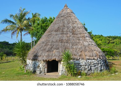 Traditional Kanak hut, tropical island vegetation and house, Isle of Pines, New Caledonia, South Pacific Ocean