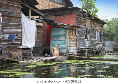 Traditional kashmiri view - old wooden houses on stilts, boat, Dal lake with duckweed, hanging laundry in Srinagar, Jammu & Kashmir, Northern India. Local people spend all their life on the water.