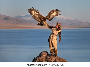 Traditional kazakh eagle hunter with his golden eagle in front of snow capped mountains at a lake shore. Ulgii, Western Mongolia.