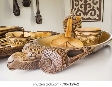Traditional Kazakh woodenware with national ornament. Big plate in a form of sheep, serving spoon & cups. Felt carpet & traditional wooden clubs in the background