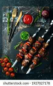 Traditional Kebab. Juicy pork skewers with vegetables on a black stone plate. Barbecue. Top view. Free space for text.