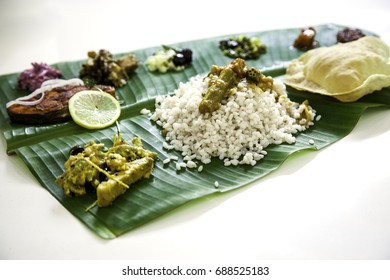 Traditional Kerala meal served in banana lea, rice, isolated on white background. Free space for text
