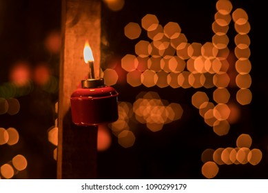 A traditional kerosene lamp  also known as pelita with light bokeh as background. Eidul fitri concept. Image contains grain and soft focus.