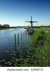 the traditional Kinderdijk wind mills of Holland in a calm water canal, bordered with water lilies