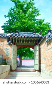 Traditional Korean architecture at Gyeongbokgung Palace. Traditional door, wall and a tree in background with blue sky. Seoul, South Korea.