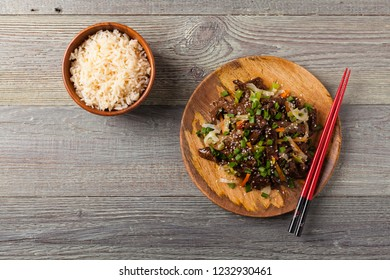 Traditional Korean Bulgogi dish.  Thinly cut, grilled beef, served with rice and vegetables. Top view. Natural wooden background.