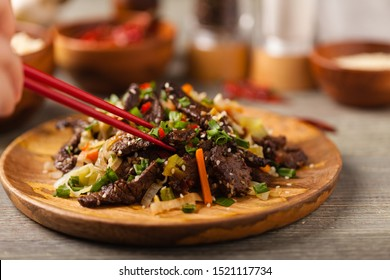 Traditional Korean Bulgogi dish.  Thinly cut, grilled beef, served with rice and vegetables. Front view. Natural wooden background.