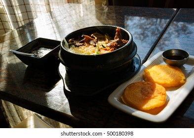 Traditional Korean dish. Bibimbap in a heated stone bowl and fried soy bean galettes. Selective focus.