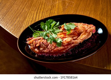 A traditional Korean dish is spicy Chinese cabbage kimchi with spices and hot sauce, served in a black plate on a wooden background. View from above