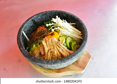 Traditional Korean food, Bibimbap rice stone bowl on wooden tray, overhead view stone roasted bibimbap on light red isolated, healthy probiotics various ingredients with raw egg yolk