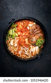 Traditional Korean kimchi jjigae with grilled pork belly and ramen as top view in a pot