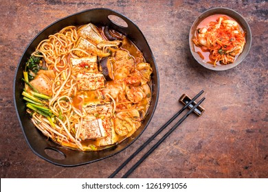 Traditional Korean kimchi jjigae with grilled pork belly and ramen as top view in a modern design Japanese cast-iron roasting dish