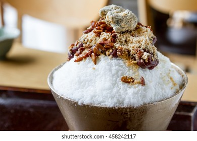 Traditional Korean Shaved Milk Ice Dessert with Sweet Red Bean, Rice Cake, and Nut Topping on a Wood Table