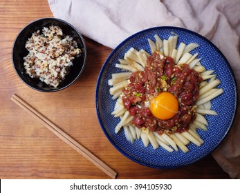 Traditional Korean style beef tartare with fresh egg yolk served with steam quinoa rice. Selective focus on egg yolk.