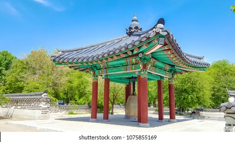 traditional Korean wooden gazebo with painted ornament and bell friendship inside